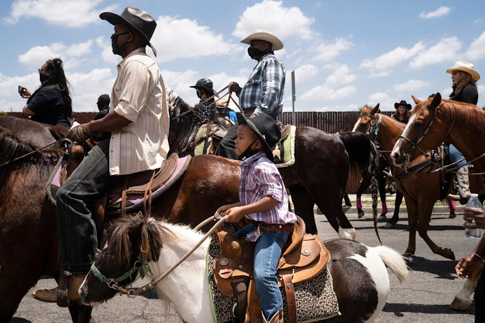 "A young boy rides with the Compton Cowboys during a ""peace ride"" for George Floyd on June 7, 2020 in Compton, California."