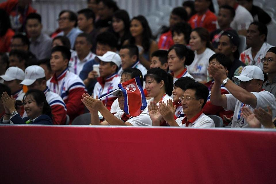 North Korean team members mingle with the public in the stands at the Jakarta International Expo during the Asian Games weightlifting (AFP Photo/CHAIDEER MAHYUDDIN)