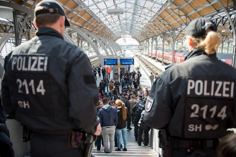 Policemen look at a group of refugees waiting on a platform of the main station in Luebeck, northern Germany, on September 8, 2015