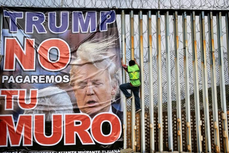 """A protestor against the  wall on the US-Mexico frontier hangs a banner reading """"Trump we will not pay for your wall"""" at Playas de Tijuana, Mexico, on February 2, 2020"""