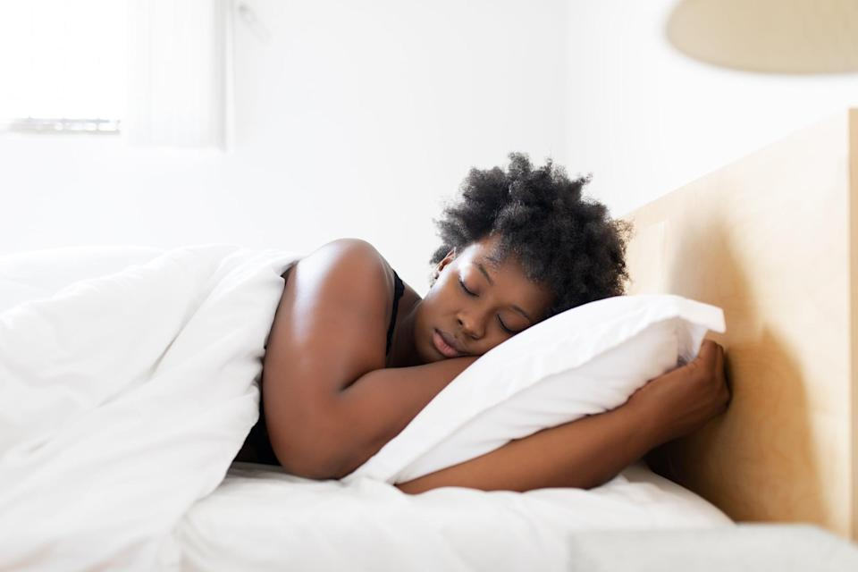 African woman sleeping in her bed. Young woman sleeping in her bed in the morning at home.