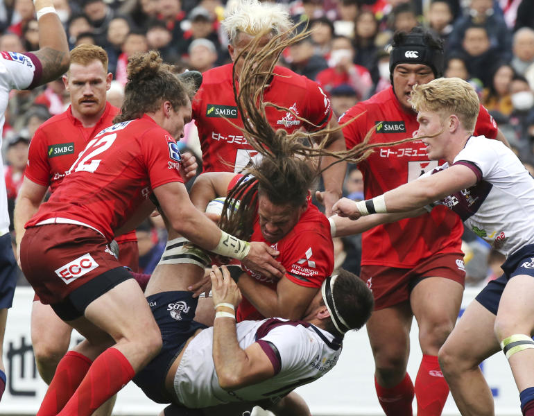 FILE - In this March 16, 2019, file photo, Dan Pryor of Sunwolves, center, holds the ball during their Super Rugby match against Reds in Tokyo. Super Rugby's governing body announced Friday, March 22, 2019 that Japan's Sunwolves will be cut from the competition at the end of the 2020 season. (AP Photo/Koji Sasahara, File)