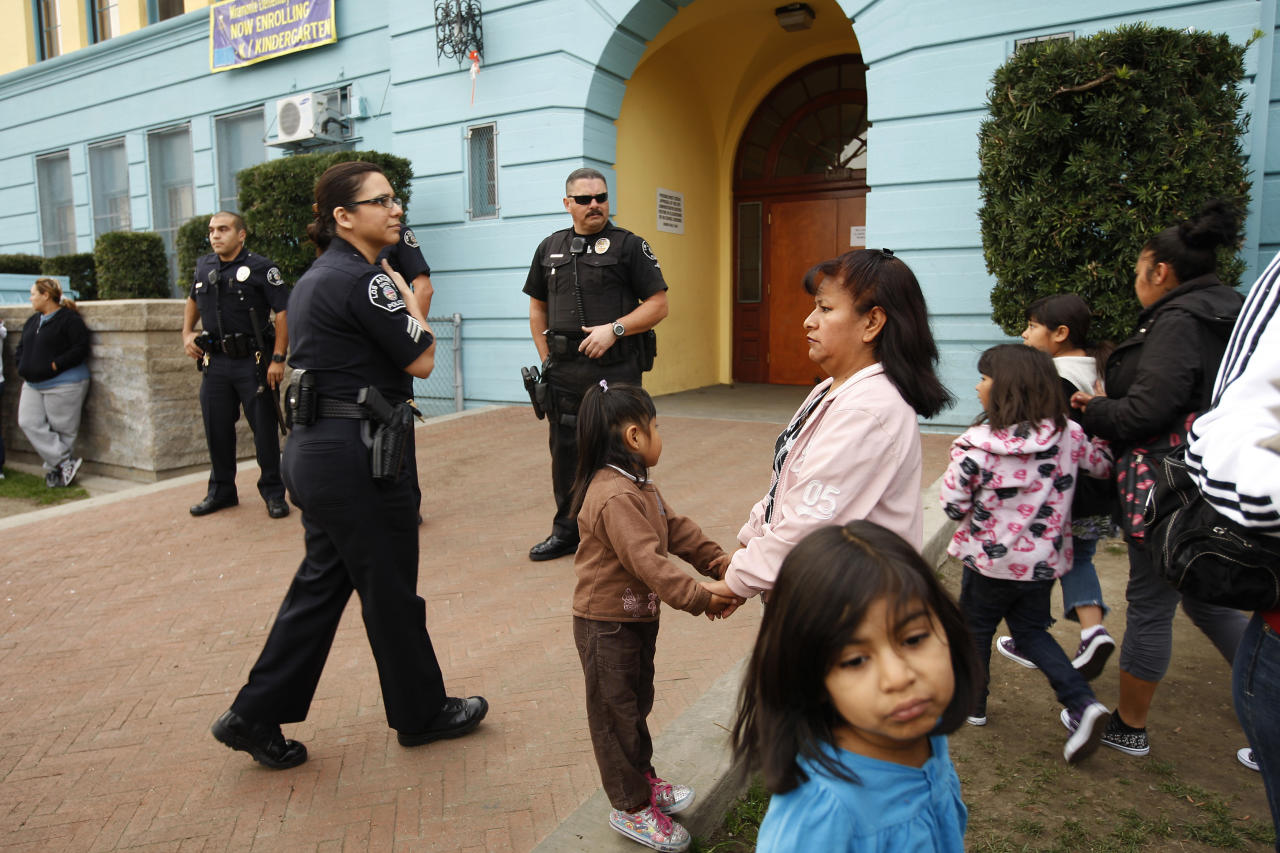 Los Angeles School Police officers provide security as parents and their children gather outside of Miramonte Elementary school to protest as the investigation continues into a bizarre sexual abuse scandal in Los Angeles, California February 6, 2012. The latest arrest, in which a teacher is accused of fondling 7 and 8-year-old girls inside his classroom, came just days after another teacher, who had worked at the school for 30 years, was arrested and charged with lewd acts involving 23 children, which included taking bondage-type photos of gagged and blindfolded students, putting cockroaches on their faces and feeding them semen. It is not known if the two alleged abuse cases are related.   REUTERS/David McNew (UNITED STATES - Tags: CRIME LAW EDUCATION)