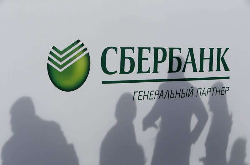 FILE PHOTO: Participants cast their shadows on a board with the logo of Sberbank at the St. Petersburg International Economic Forum