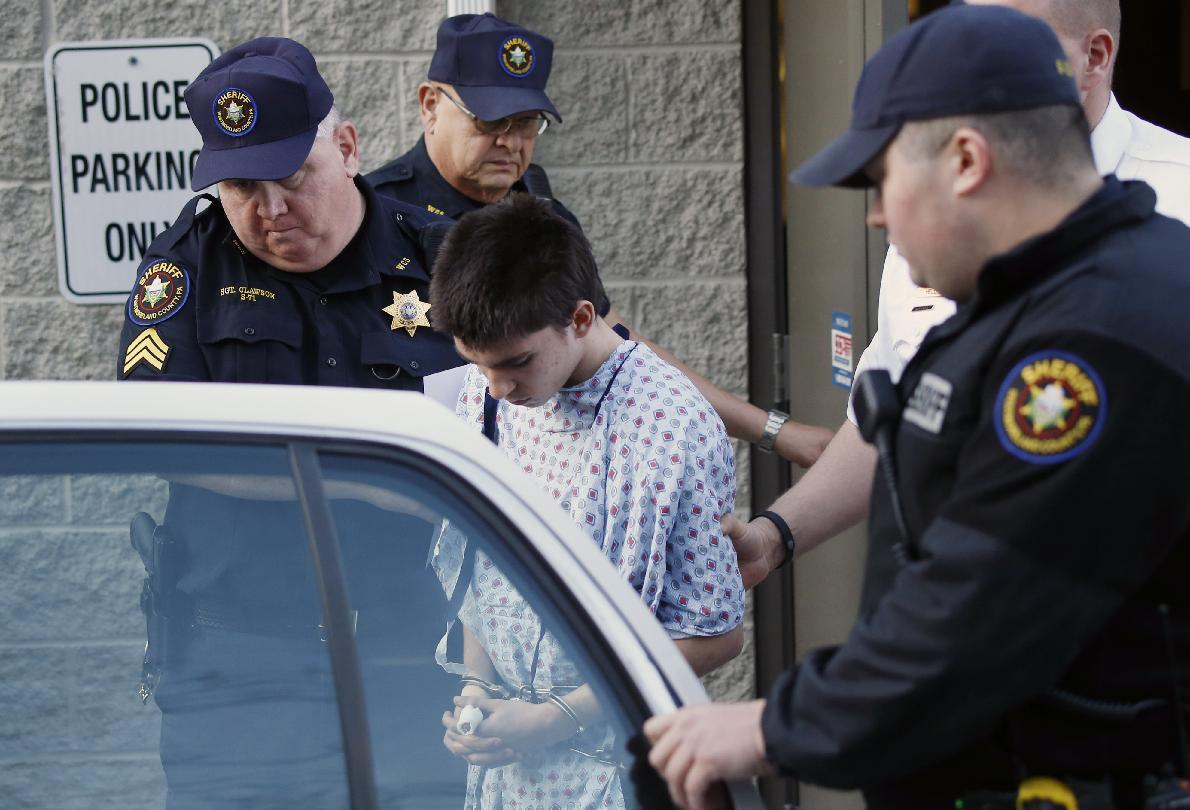Alex Hribal, center, the suspect in the stabbings at the Franklin Regional High School near Pittsburgh, is taken from a district magistrate after he was arraigned on charges in the attack on Wednesday, April 9, 2014 in Export, Pa. Authorities say Hribal has been charged after allegedly stabbing and slashing at least 19 people, mostly students, in the crowded halls of his suburban Pittsburgh high school Wednesday. (AP Photo/Keith Srakocic)