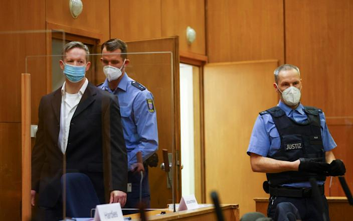 Stephan Ernst (left) arrives at the courtroom as he waits for the verdict in the case of the murder of Walter Luebcke, at the Higher Regional Court in Frankfurt - Kai Pfaffenbach/AFP