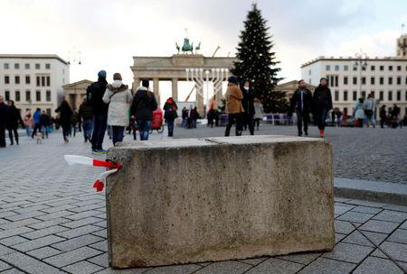 FILE PHOTO: People walk beside a concrete barrier at the Brandenburg Gate ahead of the upcoming New Year's Eve celebrations in Berlin