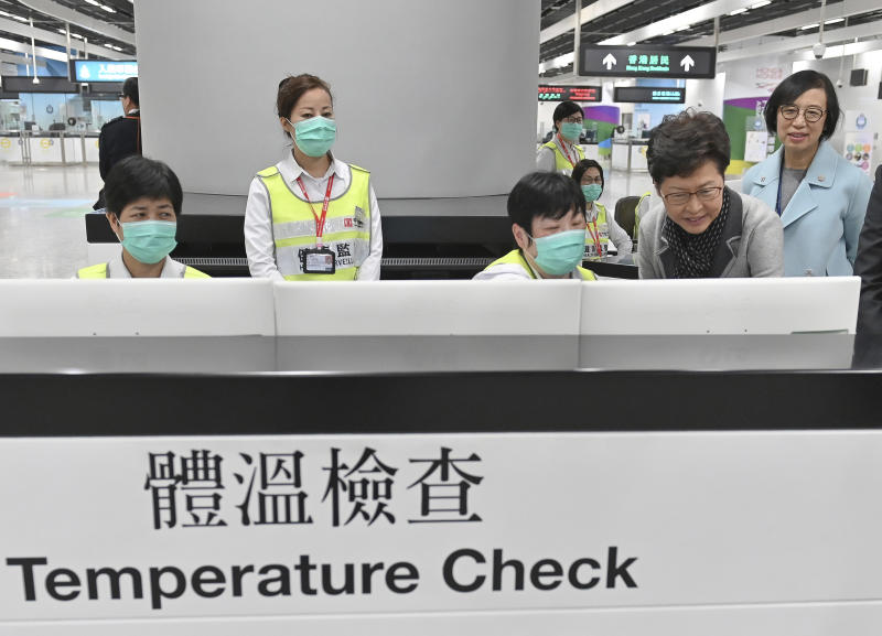 """In this Friday, Jan. 3, 2020, photo released by Hong Kong Government Information Service, Hong Kong Chief Executive Carrie Lam, second from right, accompanied by Secretary for Food and Health, Prof. Sophia Chan, right, reviews the health surveillance measures by officers of the Port Health Division at West Kowloon Station in Hong Kong. Hong Kong authorities activated a newly created """"serious response"""" level Saturday, Jan. 4, 2020, as fears spread about a mysterious infectious disease that may have been brought back by visitors to a mainland Chinese city. Lam urged any travelers who develop respiratory symptoms to wear surgical masks, seek medical attention and let doctors know where they have been. (Hong Kong Government Information Service via AP)"""