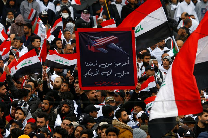 """Supporters of Iraqi Shi'ite cleric Moqtada al-Sadr hold a sign reading """"Get out of our land before you leave defeated"""" at a protest against what they say is U.S. presence and violations in Iraq, in Baghdad"""