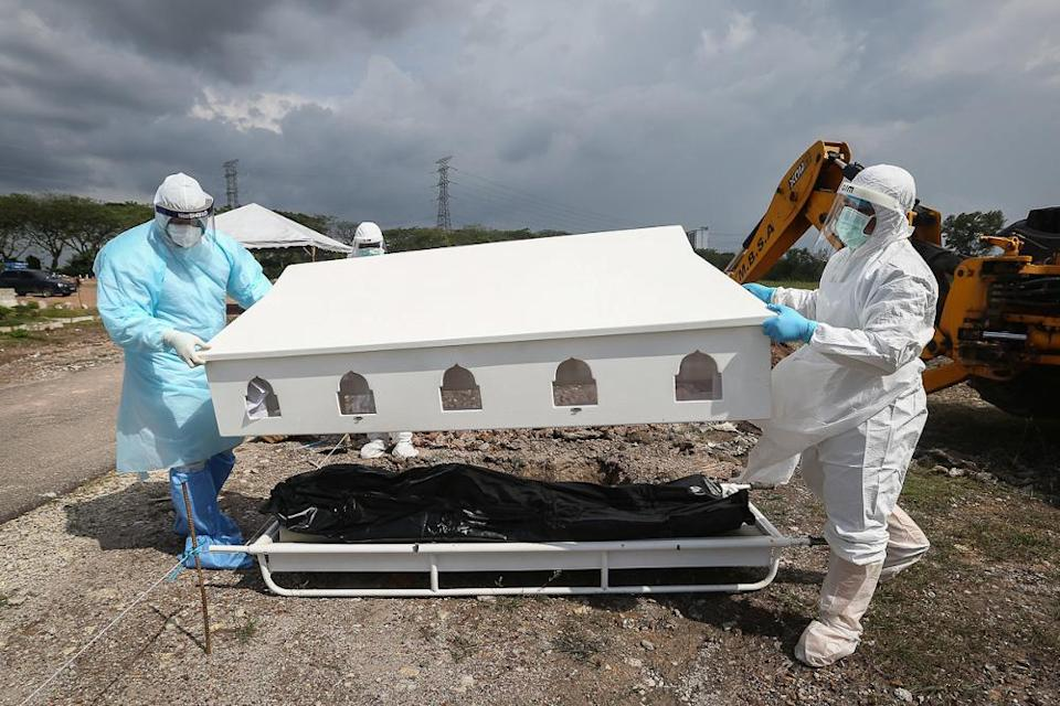 Workers wearing personal protective equipment (PPE) carry the body of a Covid-19 victim at a cemetery in Shah Alam February 11, 2021. Malaysia had hit a high of 24 deaths from Covid-19 on February 8, but this was eclipsed by the current record of 25 deaths reached on February 18. — Picture by Yusof Mat Isa