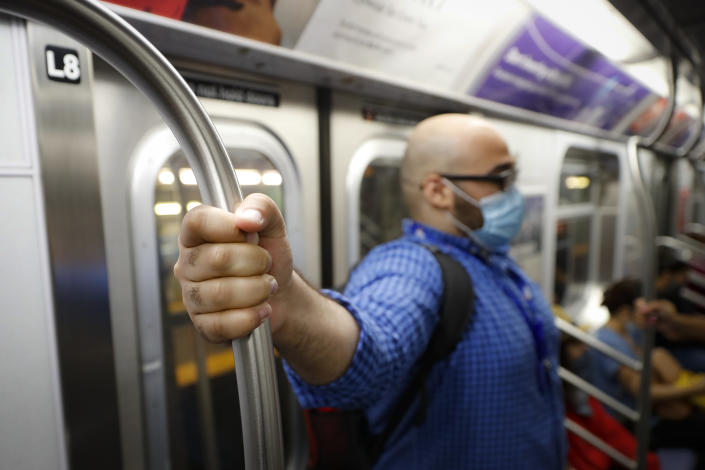 Joseph Ortiz, a contact tracer with New York City's Health + Hospitals battling the coronavirus pandemic, takes the subway system on the way to a potential patient's home Thursday, Aug. 6, 2020, in New York. The city has hired more than 3,000 tracers and the city says it's now meeting its goal of reaching about 90% of all newly diagnosed people and completing interviews with 75%. (AP Photo/John Minchillo)