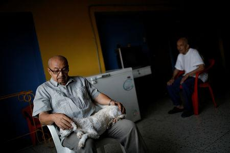 David Riveros, 62, a retired bus driver, pets his dog next to his father-in-law while they rest at home, on the 1st floor of an apartment block in downtown Caracas, Venezuela, March 19, 2019. REUTERS/Carlos Garcia Rawlins