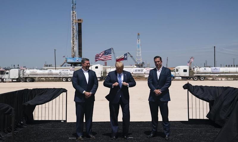 Donald Trump adjusts his jacket as he stands with Double Eagle Energy co-CEOs Cody Campbell, left, and John Sellers, right before viewing the Double Eagle Energy oil rig in Midland, Texas.