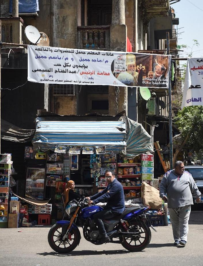 A picture taken on March 20, 2018 shows privately sponsored election banners supporting Egyptian President Abdel Fattah al-Sisi hanging in a main street in the capital Cairo's northern suburb of Shubra (AFP Photo/MOHAMED EL-SHAHED)
