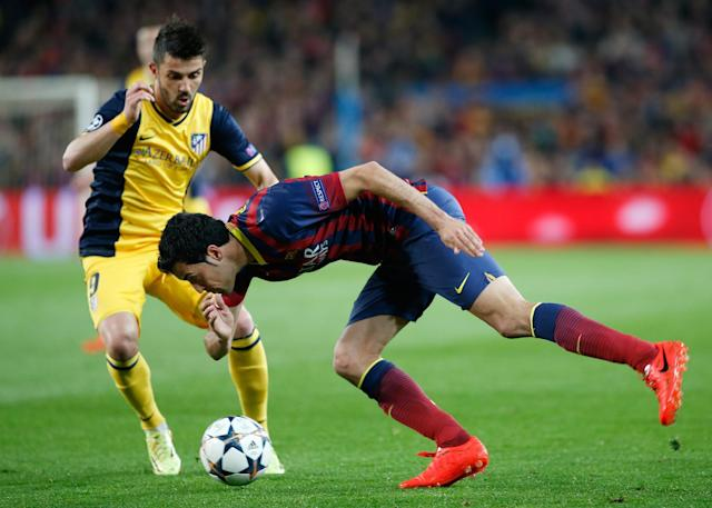 Barcelona's Sergio Busquets, right, falls in front of Atletico's David Villa during a first leg quarterfinal Champions League soccer match between Barcelona and Atletico Madrid at the Camp Nou stadium in Barcelona, Spain, Tuesday April 1, 2014. (AP Photo/Emilio Morenatti)
