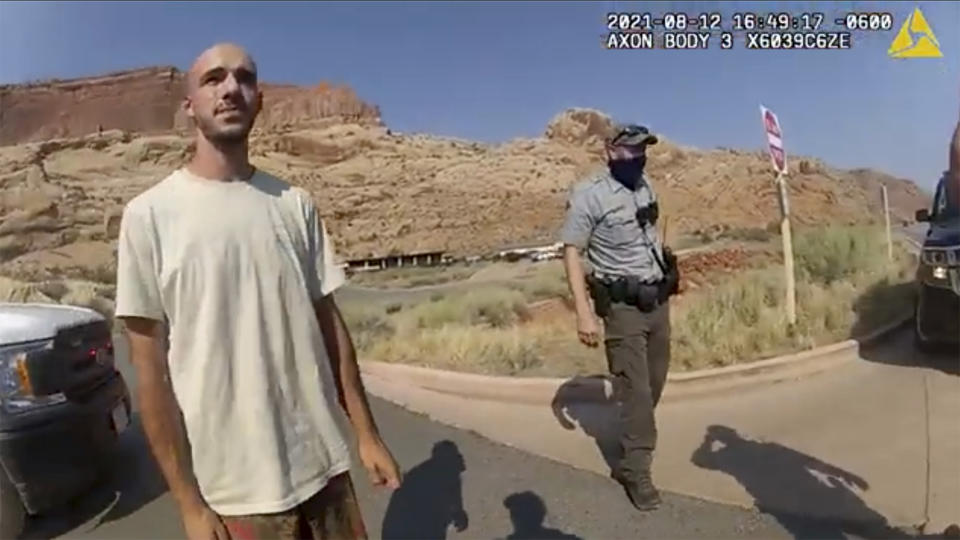 Screenshot from police camera video of Brian Laundrie and an officer standing on the street near parked vehicles in front of a rocky desert landscape.