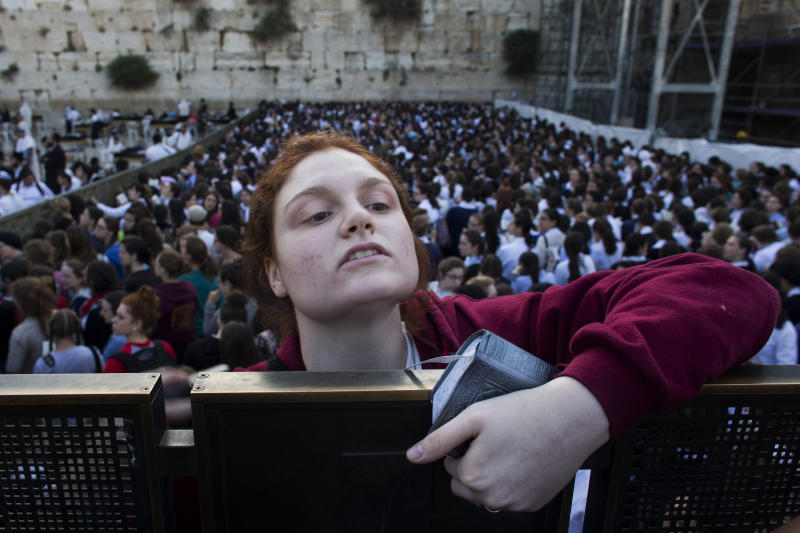 """A Jewish orthodox women follows a prayer organized by the """"Women of the Wall"""" organization, not pictured, at the Western Wall, the holiest site where Jews can pray in Jerusalem's old city, Friday, May 10, 2013. The """"Women of the Wall"""" group has been holding monthly prayer services on the first day of the Hebrew month at the Western Wall in Jerusalem for more than two decades, wearing prayer shawls and performing religious rituals reserved for men under Orthodox Judaism. Accused by ultra-Orthodox leaders of violating """"local custom"""" at the holy site, many members have been arrested. On Friday the tables were turned because of the court ruling. Police protected the women and arrested three ultra-Orthodox men for disorderly conduct, police spokesman Micky Rosenfeld said. (AP Photo/Bernat Armangue)"""