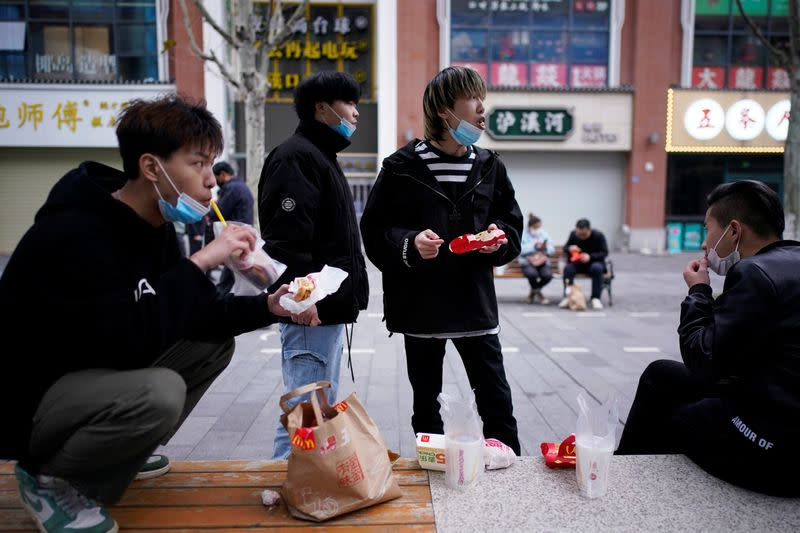 People with face masks eat outside a McDonald's restaurant in Wuhan