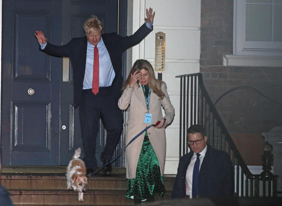 Britain's Prime Minister and Conservative Party leader Boris Johnson leaves Conservative Party headquarters with his partner Carrie Symonds and their dog Dilyn, in London, Friday, Dec. 13, 2019. Prime Minister Boris Johnson's Conservative Party appeared on course Friday to win a solid majority of seats in Britain's Parliament— a decisive outcome to a Brexit-dominated election that should allow Johnson to fulfill his plan to take the U.K. out of the European Union next month. (AP Photo/Thanassis Stavrakis)