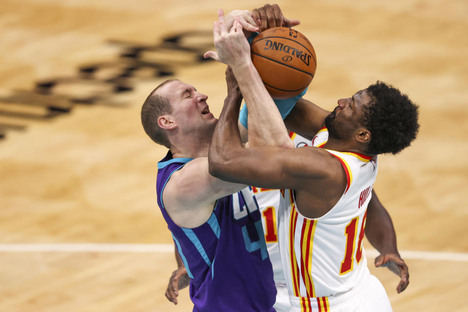 Charlotte Hornets center Cody Zeller, left, and Atlanta Hawks forward Solomon Hill, right, battle for the ball during the third quarter of an NBA basketball game in Charlotte, N.C., Sunday, April 11, 2021. (AP Photo/Nell Redmond)