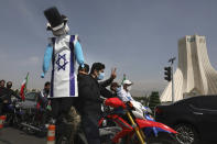 A demonstrator on a motorcycle holds an effigy representing Israel and the United States during the annual Al-Quds, or Jerusalem, Day rally, with the Azadi (Freedom) monument tower seen at right, in Tehran, Iran, Friday, May 7, 2021. Iran held a limited anti-Israeli rally amid the coronavirus pandemic to mark the Quds Day. After the late Ayatollah Khomeini, leader of the Islamic Revolution and founder of present-day Iran, toppled the pro-Western Shah in 1979, he declared the last Friday of the Muslim holy month of Ramadan as an international day of struggle against Israel and for the liberation of Jerusalem. (AP Photo/Vahid Salemi)