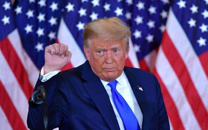 US President Donald Trump pumps his fist after speaking during election night in the East Room of the White House - AFP