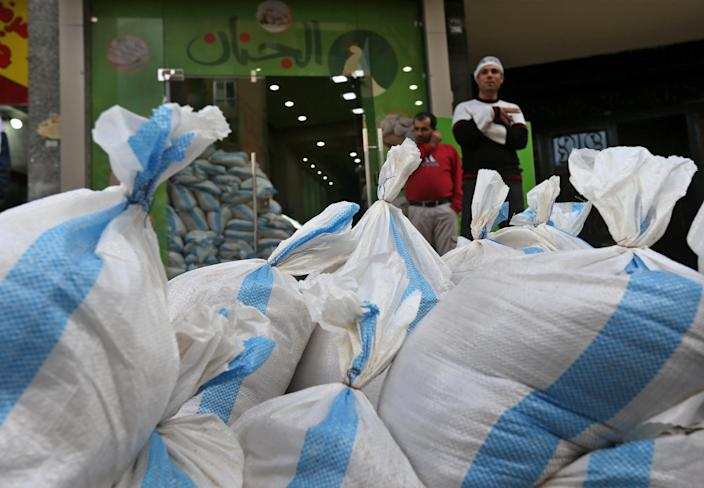 FILE - In this Tuesday, Jan. 28, 2014 file photo, sandbags are piled in front of a chicken shop to be set as sand barriers in a Shiite neighborhood of a southern suburb of Beirut, Lebanon. After a wave of car bomb attacks on Hezbollah's stronghold south of Beirut that left scores of people dead or wounded over the past three months, shop owners scared of more bombs have set up sand barriers in front of their institutions to reduce damage in case more blasts occur. The attacks that hit the south Beirut area known as Dahiyeh (suburb) has sacred many people in the area and increased security measures by Lebanese troops and members of the militant group.(AP Photo/Hussein Malla, File)