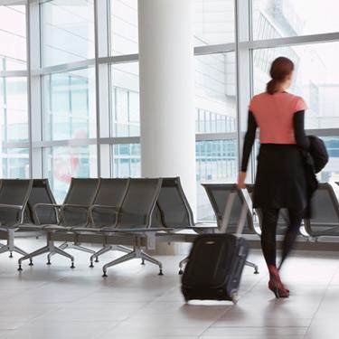 Woman-pulling-suitcase-through-airport_web
