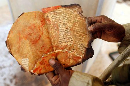 A museum guard displays a burnt ancient manuscript at the Ahmed Baba Institute, or Ahmed Baba Centre for Documentation and Research, in Timbuktu  January 31, 2013.  REUTERS/Benoit Tessier/Files