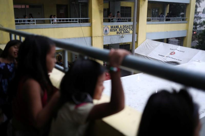 Children look on at the Delpan Evacuation Center after Typhoon Kammuri hit Metro Manila