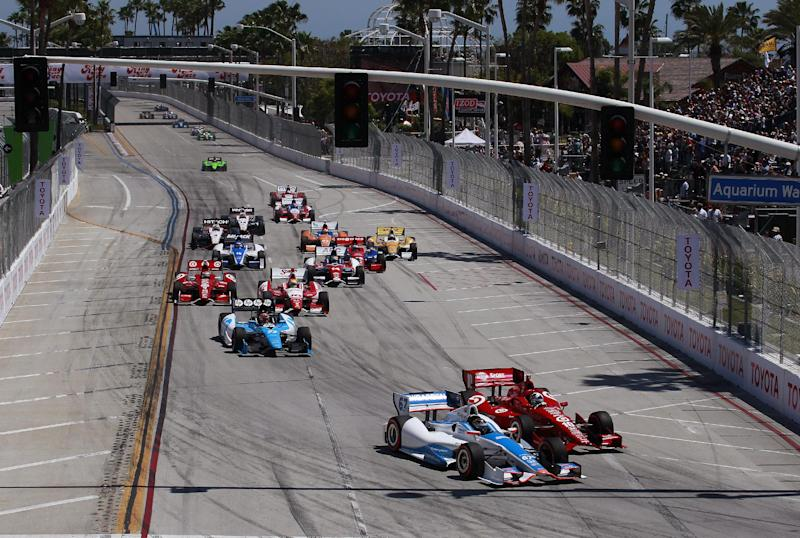 Josef Newgarden (67) attempts a pass on Dario Franchitti (10), of Scotland, heading into the first turn at the start of the IndyCar Series' Long Beach Grand Prix auto race, Sunday, April 15, 2012, in Long Beach, Calif. Newgarden hit a tire barrier, and was out of the race. (AP Photo/LAT, Michael L. Levitt)
