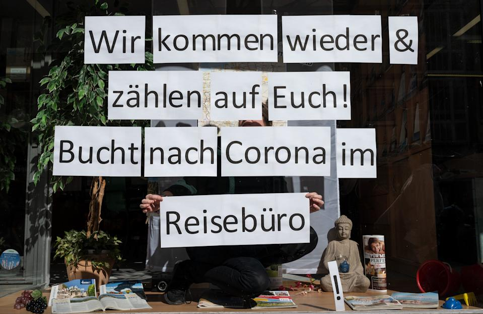 """23 March 2020, North Rhine-Westphalia, Dortmund: An employee of a travel agency sticks individual sheets of paper with the inscription """"We will come back & count on you! Bucht nach Corona im Reisebüro"""" into the shop window. Collections of more than two people are prohibited throughout Germany, shops and restaurants are closed. Photo: Bernd Thissen/dpa (Photo by Bernd Thissen/picture alliance via Getty Images)"""