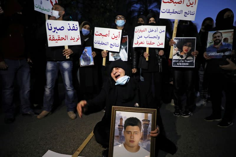 Families of some of the victims of the August 4 explosion at Beirut port, carry their pictures and sing during a protest outside the Justice Palace in Beirut