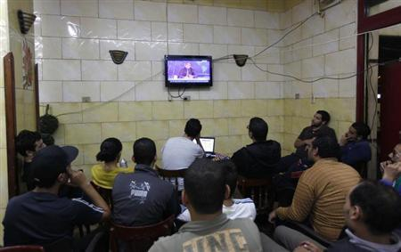 Egyptians watch the first episode of a show by Egypt's most prominent television satirist, Bassem Youssef, called Al-Bernameg in Cairo