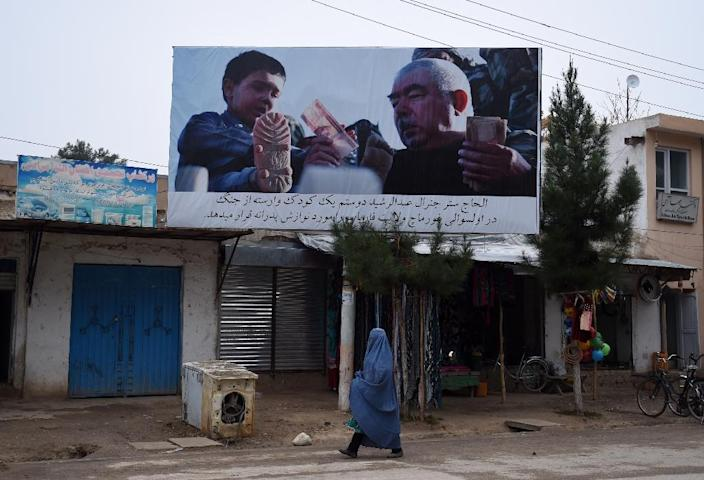 An Afghan woman walks under a poster bearing the image of vice-president general Abdul Rashid Dostum along the road in Maimana, the capital of the northern province of Faryab (AFP Photo/Wakil Kohsar)