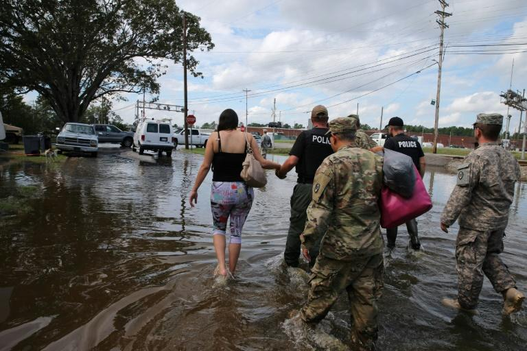 Members of police and North Carolina National Guard assist a pregnant woman in Lumberton, North Carolina