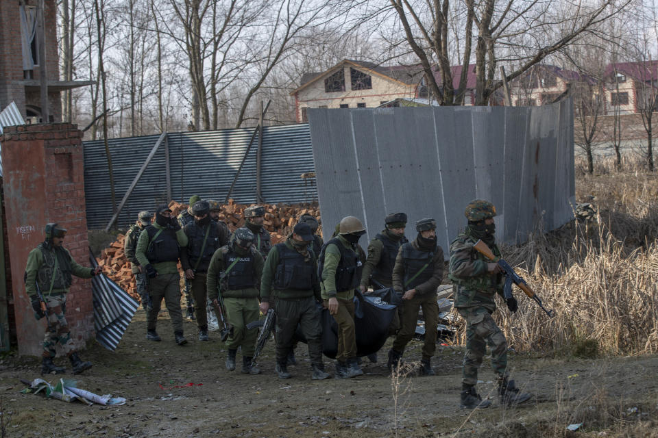 Indian policemen carry the body of a suspected rebel after a gun battle on the outskirts of Srinagar, Indian controlled Kashmir, Wednesday, Dec. 30, 2020. A gun battle between rebels and government forces overnight killed three rebels on the outskirts of Srinagar on Wednesday, officials said. (AP Photo/ Dar Yasin)