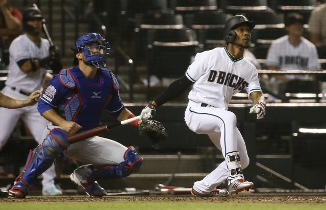 Arizona Diamondbacks' Jarrod Dyson, right, watches his walk-off, two-run home run next to Texas Rangers catcher Jeff Mathis during a baseball game Tuesday, April 9, 2019, in Phoenix. The Diamondbacks won 5-4. (AP Photo/Ross D. Franklin)