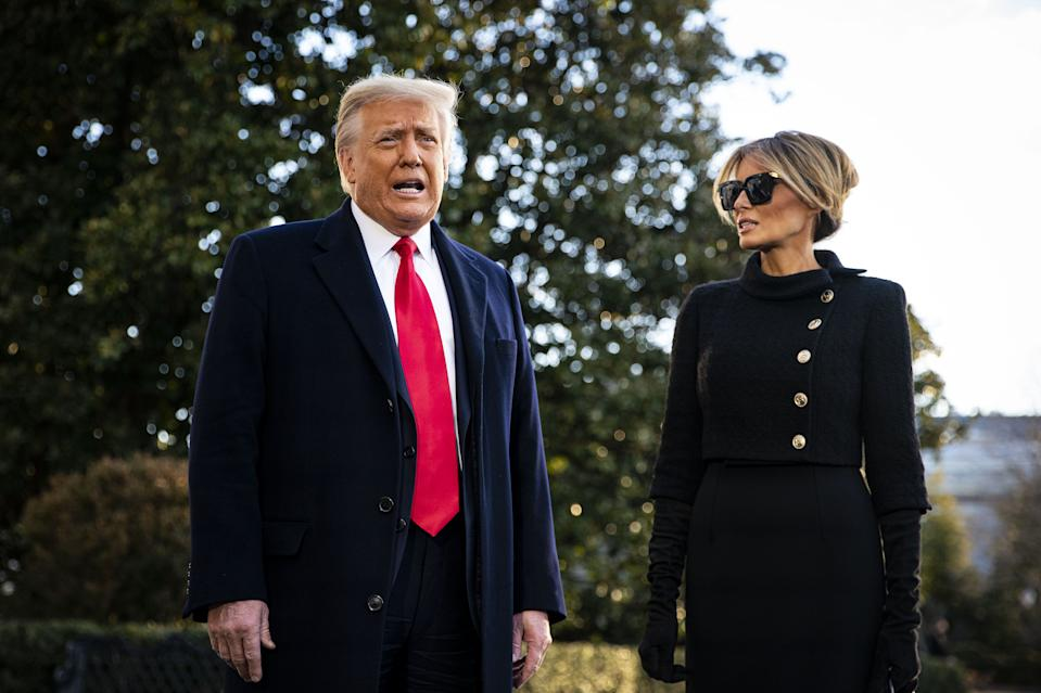 U.S. President Donald Trump, left, speaks to members of the media next to U.S. First Lady Melania Trump before boarding Marine One on the South Lawn of the White House in Washington, D.C., U.S., on Wednesday, Jan. 20, 2021. Trump departs Washington with Americans more politically divided and more likely to be out of work than when he arrived, while awaiting trial for his second impeachment - an ignominious end to one of the most turbulent presidencies in American history.