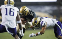 Colorado quarterback Steven Montez, center, is stopped after a short gain by Washington defensive back Myles Bryant, right, as defensive back Cameron Williams comes in to cover during the first half of an NCAA college football game Saturday, Nov. 23, 2019, in Boulder, Colo. (AP Photo/David Zalubowski)