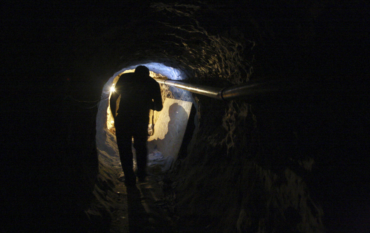 "A journalist walks through a tunnel during a presentation to the media in Tijuana November 16, 2011. Police have discovered a ""major cross-border drug tunnel"" running to California from Mexico, and seized 14 tons of marijuana, authorities said Wednesday. The tunnel links warehouses in an industrial park south of San Diego and the Mexican border city of Tijuana, the U.S. Immigration and Customs Enforcement agency said in a news release.  REUTERS/Jorge Duenes (MEXICO - Tags: CRIME LAW DRUGS SOCIETY)"