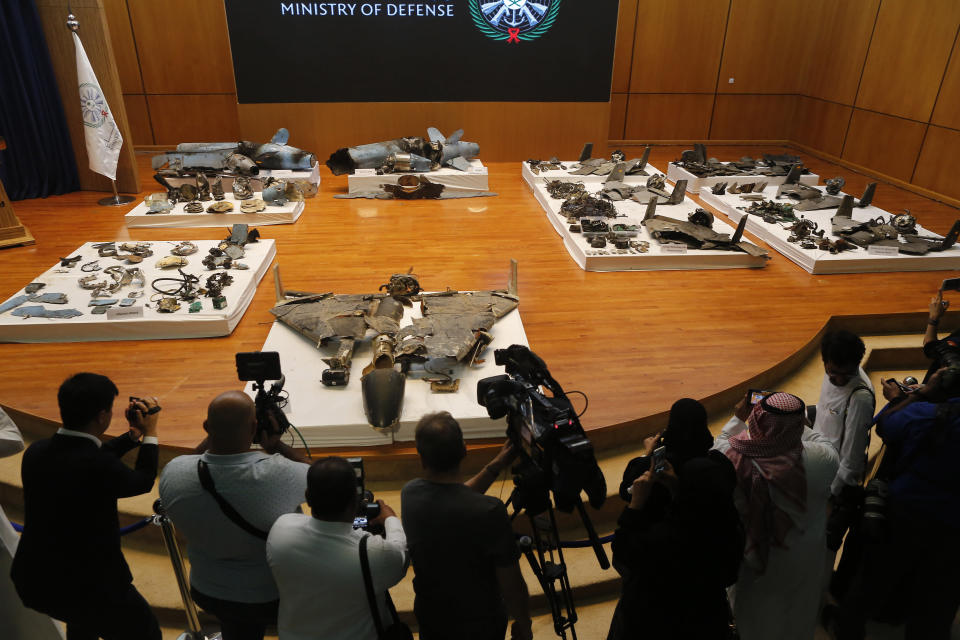 Journalists film what Saudi military spokesman Col. Turki al-Malki said was evidence of Iranian weaponry used in the attack targeted Saudi Aramco's facilities in Abqaiq and Khurais, during a press conference in Riyadh, Saudi Arabia, Wednesday, Sept. 18, 2019. (AP Photo/Amr Nabil)