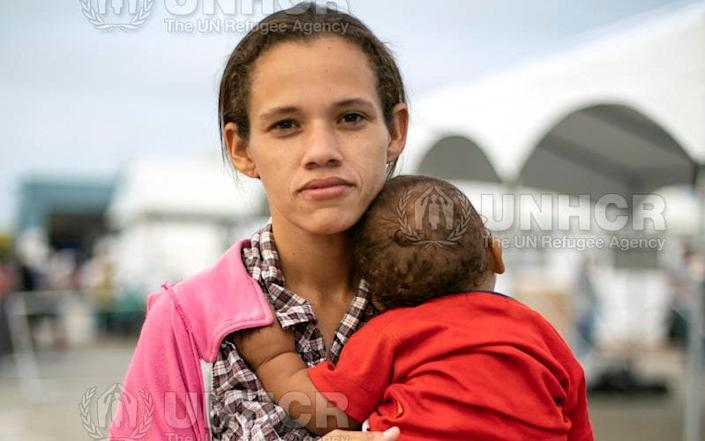 Daniela, 29, with her 10-month-old baby at the Ecuador-Peru border after fleeing Venezuela with her husband and two children. - UNHCR