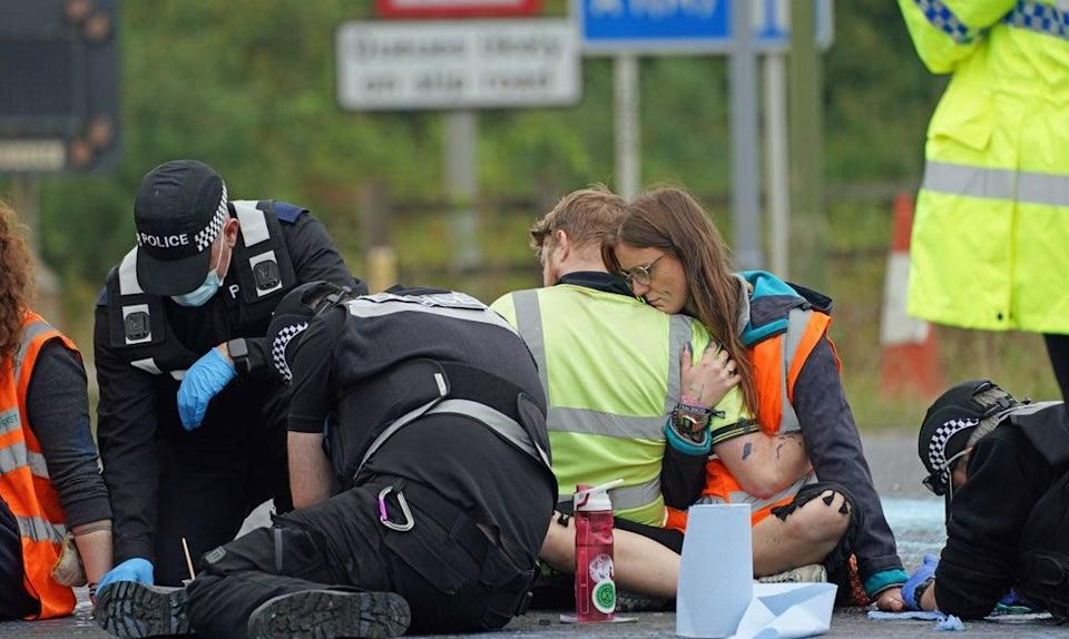 Police officers work to free protesters who had glued themselves to the highway at a slip road at junction four of the A1(M), near Hatfield (Steve Parsons/PA) (PA Wire)