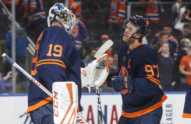 Edmonton Oilers goalie Mikko Koskinen (19) and teammate Connor McDavid (97) celebrate the team's 2-1 win over the Los Angeles Kings in an NHL hockey game Friday, Dec. 6, 2019, in Edmonton, Alberta. (Jason Franson/The Canadian Press via AP)