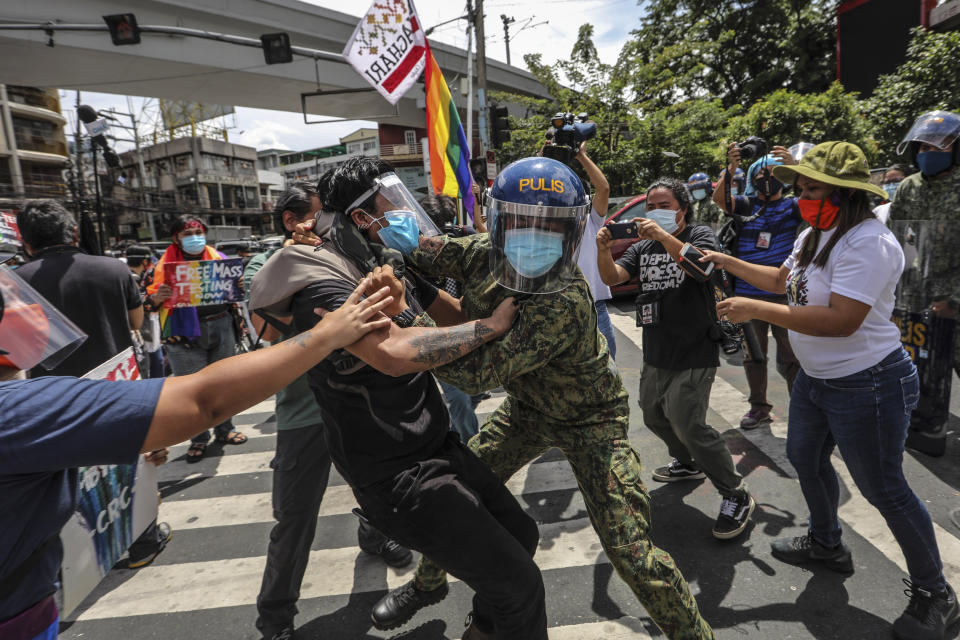 FILE PHOTO: Police wearing face masks arrest protesters during a LGBTQ pride march in Manila, Philippines, Friday June 26, 2020. Philippine police  arrested 20 protesters who marked the Global Pride event with a march to demand government aid for poor workers and drivers displaced by the coronavirus lockdown. (AP Photo/Gerard Carreon)