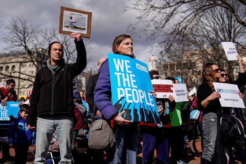 People hold signs during a demonstration against U.S. President Donald Trump on President's day near the White House in Washington, Feb. 18, 2019. (Photo: Joshua Roberts/Reuters)