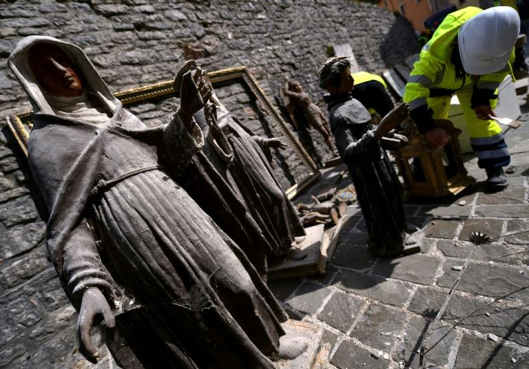 "A volunteer on the ""blue helmet"" brigade to rescue historic artwork cleans statues recovered from the San Francesco di Visso"