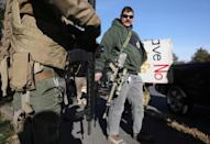 """Men carry rifles as militia members and pro-gun rights activists participating in the """"Declaration of Restoration"""" rally prepare to march to Washington, D.C. from Arlington, Virginia"""