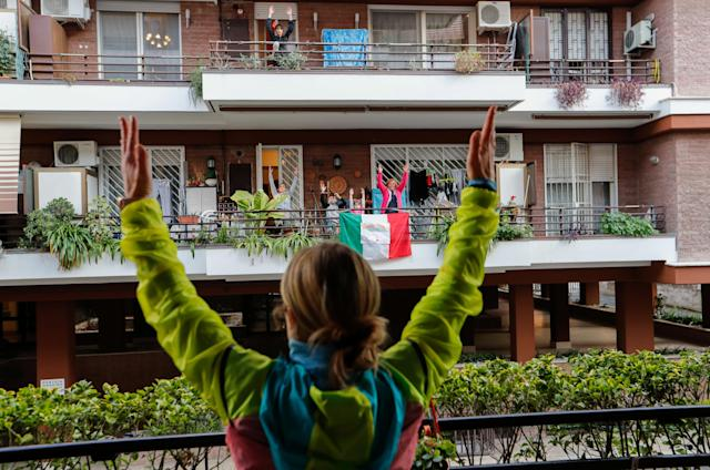A personal trainer leads an exercise class for her neighbours from her balcony in Rome, as Italians are unable leave their homes due to the coronavirus crisis. (Reuters/Remo Casilli)